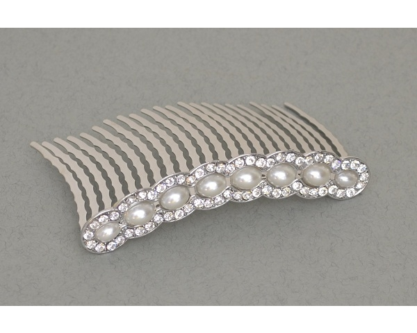 A row of large pearl beads surrounded by crystal stones on a comb